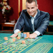 Gambler stakes playing roulette at casino table — Stock Photo #21254235