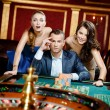 Stock Photo: Man with two girls playing roulette at the casino club