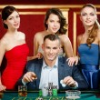 Man surrounded by ladies plays roulette - ストック写真