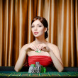 Stock Photo: Female gambler sitting at casino table