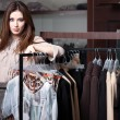 Pretty woman is in the ready-made clothes shop — Stock Photo #21255035