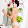 Woman with red apple near the opened fridge — Stock Photo #21259639