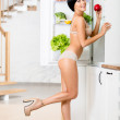 Full-length portrait of woman near the opened refrigerator — Stock Photo #21259651