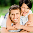 Couple lying on the grass embraces each other — Stock Photo