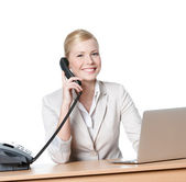 Young businesswoman sitting at a desk and talking by phone — Stock Photo