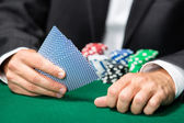 Gambler playing cards with poker chips on the table — Stock Photo