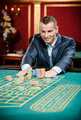 Gambler stakes playing roulette at the casino table — Stock Photo