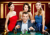 Man surrounded by ladies plays roulette — Stok fotoğraf