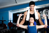 Personal trainer helps woman to exercise with weights — Stock Photo