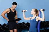 Trainer controls sports actions of pretty woman — Stock Photo