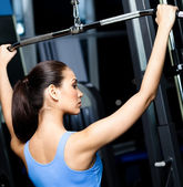 Athletic young woman works out on gym equipment — Stock Photo