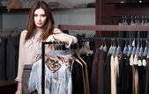 Pretty woman is in the ready-made clothes shop — Stock Photo