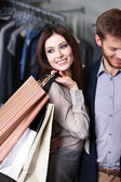 Glad woman is in the shop with boyfriend — Stock Photo