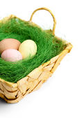 Colored easter eggs are in braided basket — Stock Photo