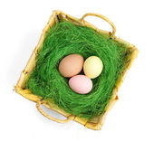 Colored easter eggs are in wattled basket — Stock Photo