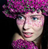 Zbliżenie niebieskooka kobiety z kwiatami — Zdjęcie stockowe