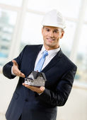 Contractor pointing at model house — Stock Photo