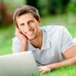 Man lying on the grass works at the laptop — Stock Photo
