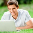 Man lying on the green grass works at the laptop — Stock Photo