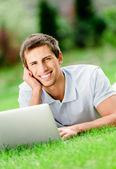 Mann liegt auf dem rasen arbeitet an den laptop — Stockfoto