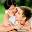 Couple lying on the green grass embraces each other — Stock Photo