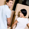 Back view of couple carrying cardboard packages — Stock Photo