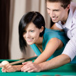 Man teaching young woman to play billiards — Stock Photo