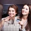 Women pay with credit card and take away bargains — Stock Photo