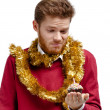 Disappointed man with tinsel holds small cake — Stock Photo