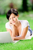 Girl lying on the grass works at the laptop — Stock Photo