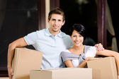 Happy couple carrying pasteboard containers — Stock Photo