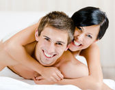 Close up of laughing couple who plays in bed-room — Stock Photo