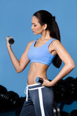 Athletic girl exercises with dumbbells — Stock Photo