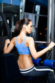 Athletic young woman works out on training apparatus — Stock Photo