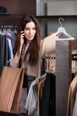 Speaking on the mobile phone and choosing clothes — Stock Photo