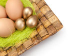 Brown and golden easter eggs are on wattled plate — Stock Photo