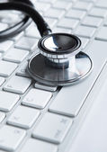 Close up of stethoscope on pc keyboard — Foto Stock