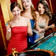 Three women playing roulette - Foto Stock