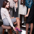 Seeking counsel from friends while trying on new fuchsia shoes — Stock Photo