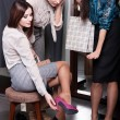Stock Photo: Seeking counsel from friends while trying on new fuchsishoes
