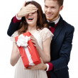 Man closes eyes of his girlfriend to give a present in red box — Foto Stock