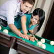 Man teaching woman to play billiards — Stock Photo