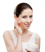 Woman putting on moisture cream from container on face — Stock Photo