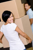 Back view of woman carrying cardboard boxes — Stock Photo