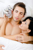 Close up view of couple lying in bed with alarm clock — Stock Photo