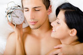 Close-up of couple lying in bed with alarm clock — Stock Photo