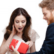 Young man amazes his pretty girlfriend with present — Stock Photo