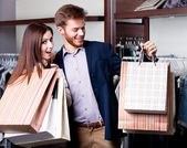 Couple with paper bags is in the shop — Stock Photo