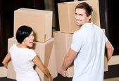 Back view of couple carrying pasteboard containers — Stock Photo