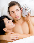 Close up of couple lying in bed with alarm clock — Stock Photo